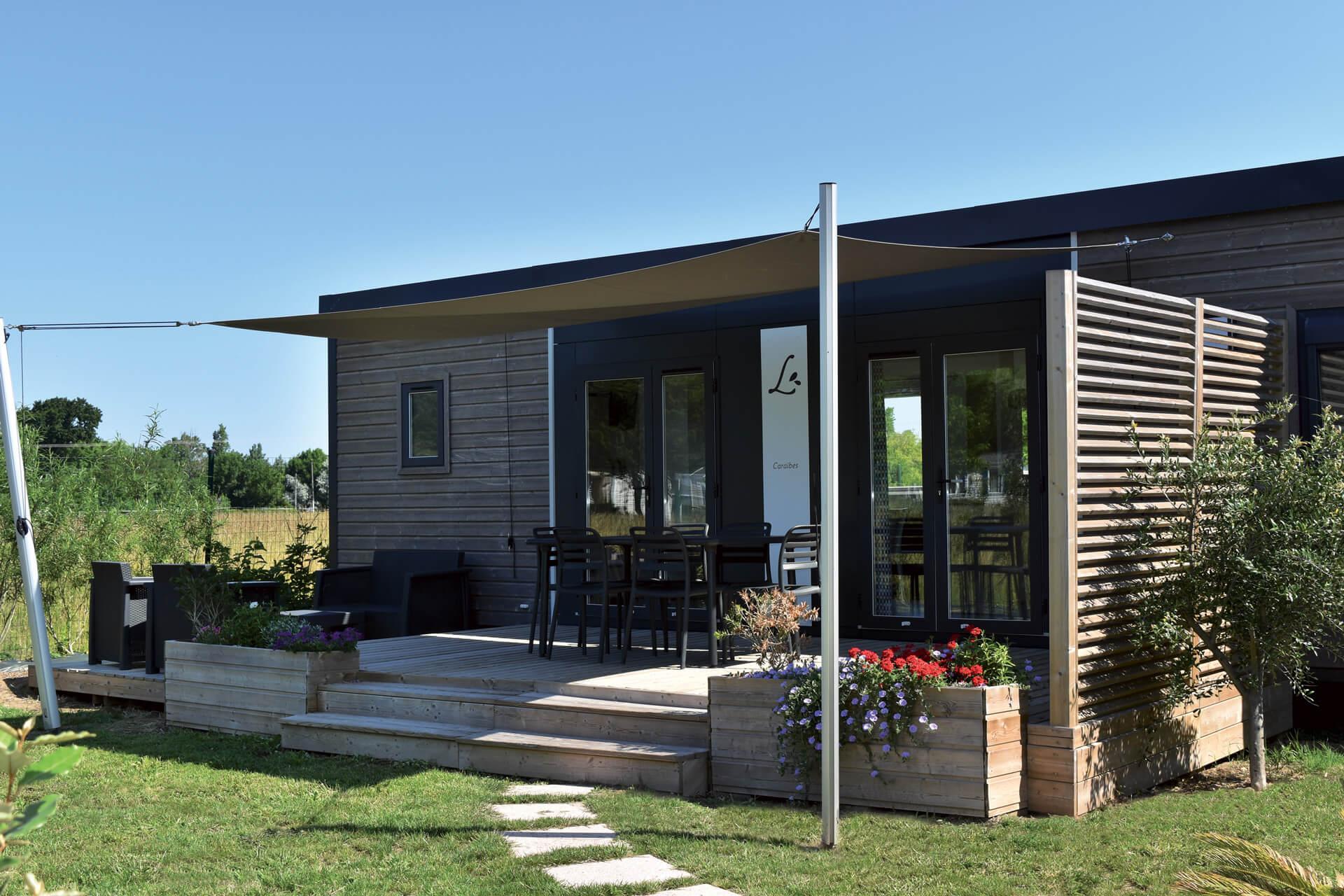 Terrasse en bois premium avec une voile d'ombrage réalisée par Les Terrasses du Lys
